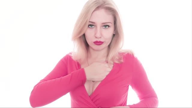vidéos et rushes de sexy confiant jeune femme blonde confiante dans une robe rouge avec un décolleté profond regardant dans la caméra, fixant son maquillage, puis redresse sa poitrine avec ses mains et laissant le cadre - décolleté