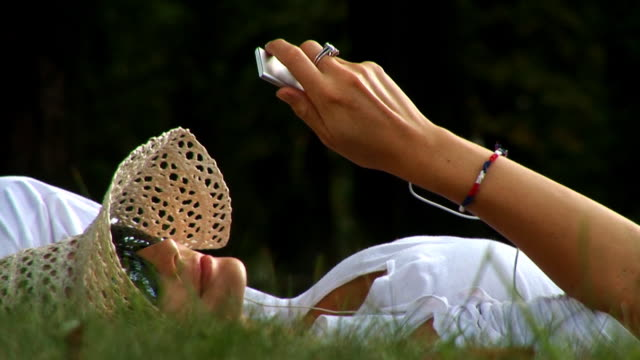 vidéos et rushes de sexy fille européen à l'écoute de musique dans le parc - allongé sur le dos