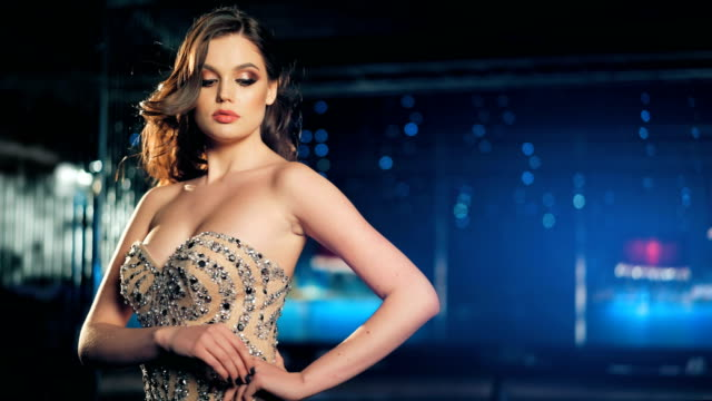 Sexy fashionable beautiful young woman in golden shining evening dress posing on night neon lights background Sexy fashionable beautiful young woman in golden shining evening dress posing on night neon lights background. dress stock videos & royalty-free footage