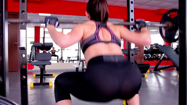 Sexy female athlete wearing tight leggings doing squats with barbell video