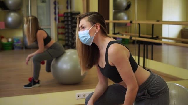 stockvideo's en b-roll-footage met de sexy vrouwelijke trainer van de sportgeschiktheid die wit medisch beschermend masker draagt oefening met rode halterzitting voor spiegel in lege gymnastiek. we zijn sterk om coronavirus covid-19 te stoppen - mirror mask