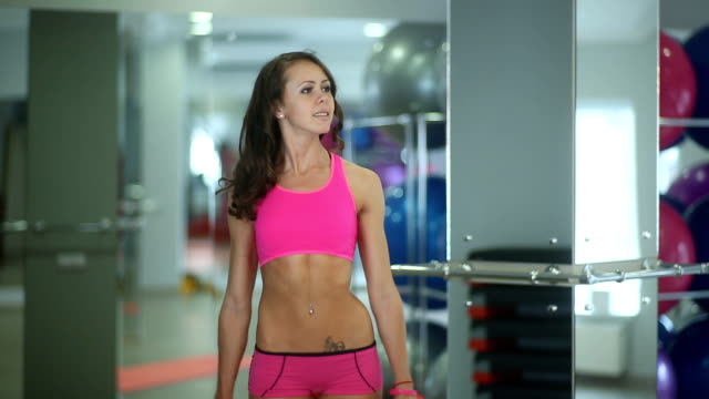 sexy fitness girl bent and doing exercises at the gym with dumbbells, attractive with beautiful legs, waist, elastic buttocks, pink clothes, a beautiful face and figure, working out - side view video