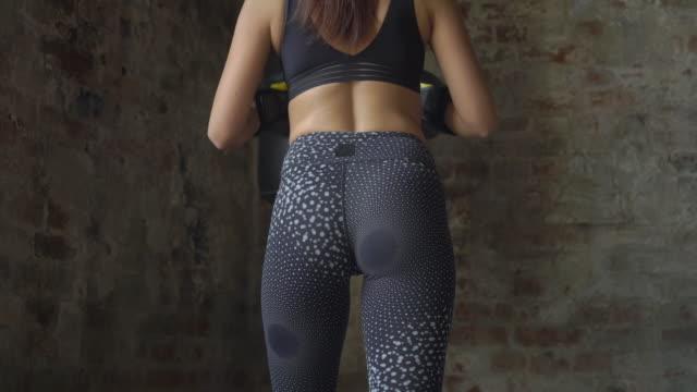 sexy fitness woman in black sportswear training with punching bag - sacco per il pugilato video stock e b–roll