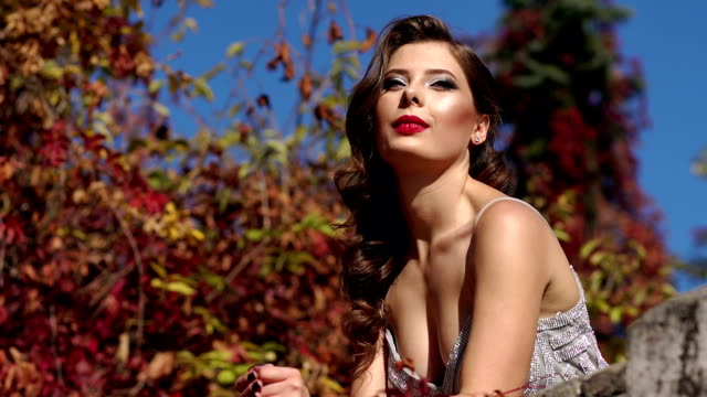 A sexy girl in an evening dress walks in an autumn park in warm weather.