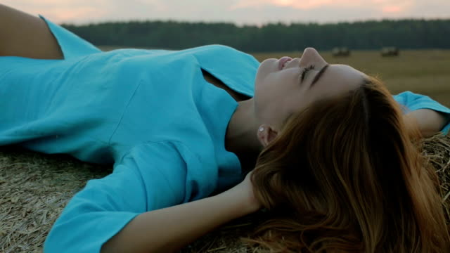 sexy girl in blue dress lying in the hay. - bassino video stock e b–roll