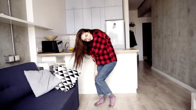 Sexy girl in her 20's is dancing in her cozy apartment, enjoying youth. video