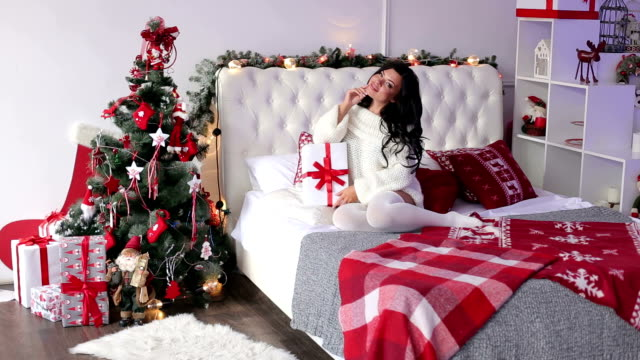 Sexy girl with Christmas present sits on the bed. video