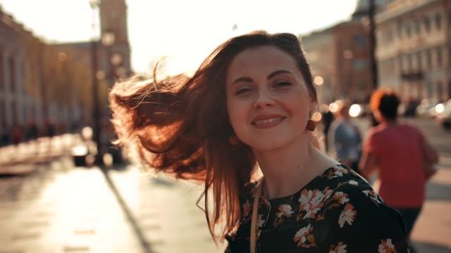 etrafında dönen ve açık kameraya gülümseyen uzun kızıl saçlı seksi kız - çekici insanlar stok videoları ve detay görüntü çekimi