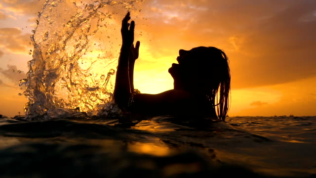 Sexy girl with wet hair and lips in the sunset in the water underwater