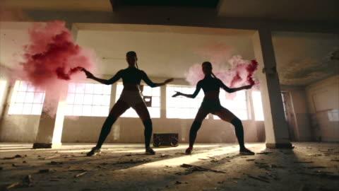 ragazze sexy che ballano con fumogeni rosa - disinvolto video stock e b–roll
