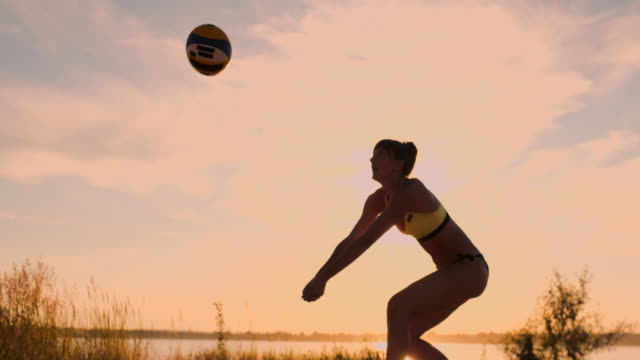 vídeos de stock e filmes b-roll de sexy girls volleyball players pass the ball near the net and hit the ball at sunset in slow motion - campeão desportivo