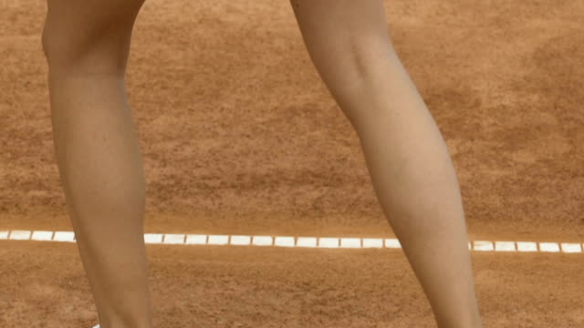 Sexy lady in short skirt preparing to play tennis, swinging racket, closeup video