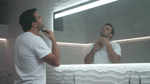 Sexy man shaving beard in bath. Grooming of serious man shaving in bathroom.