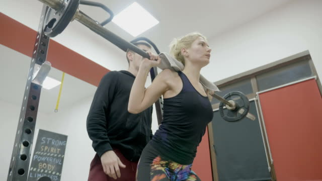 Sexy pretty blonde fitness girl exercising with weights in a gym helped by her personal male trainer video