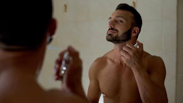 sexy smiling man spraying perfume on body bathroom, preparing for romantic date - profumato video stock e b–roll