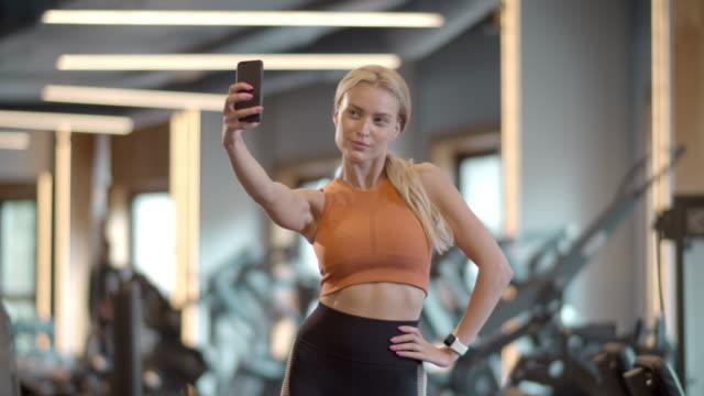 stockvideo's en b-roll-footage met sexy sportvrouw die selfiefoto in sportclub maakt. vrouwelijke atleet die bij gymnastiek stelt - call center