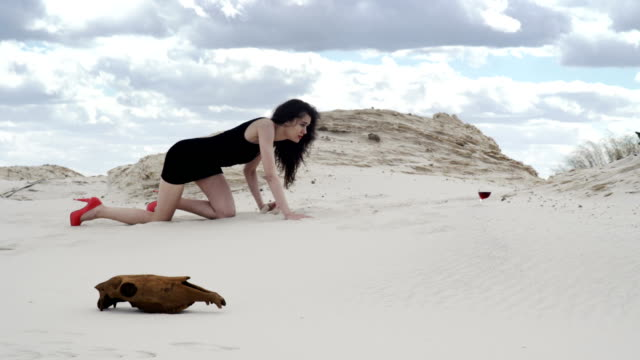 Sexy Woman Crawling in Desert Young Woman in a Cocktail Dress Crawling in Desert to the a glass of wine with an animal Skull in the Foreground skull stock videos & royalty-free footage