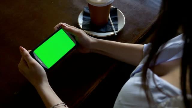 sexy frau mit smartphone mit green-screen beim sitzen in einem restaurant - tablet mit displayinhalt stock-videos und b-roll-filmmaterial