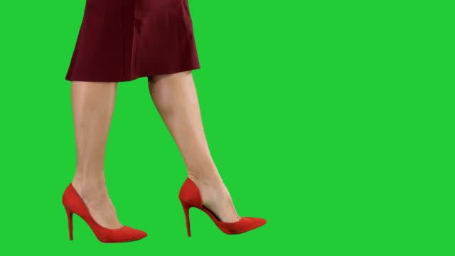 vídeos de stock, filmes e b-roll de pernas de mulher sexy de saltos altos vermelhos andando senhora de negócios em uma tela verde, chroma key - salto alto