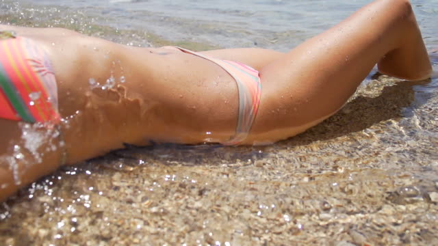 HD SUPER SLOW MO: Sexy Woman Lying On The Beach HD1080p: SUPER SLOW MOTION shot of a young woman enjoying the waves splashing her body on the beach. Panning shot. sunbathing stock videos & royalty-free footage