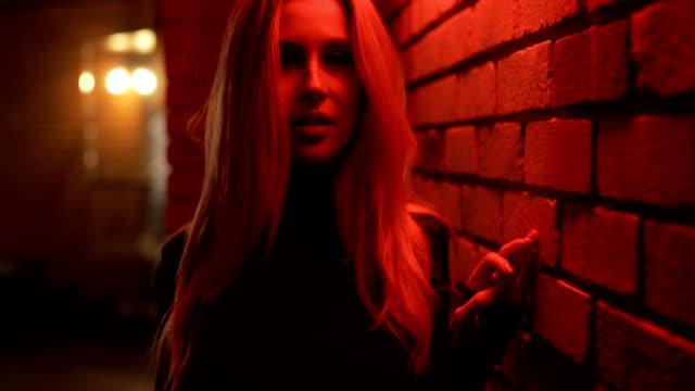 stockvideo's en b-roll-footage met sexy vrouw poseren bij rood licht muur - verleiding