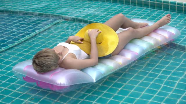 """vídeos de stock, filmes e b-roll de mulher """"sexy"""" que dorme no flutuador inflável que relaxa na piscina. a senhora nova com o chapéu amarelo que encontra-se para baixo no colchão de ar toma um sunbath em férias de verão. - inflável"""