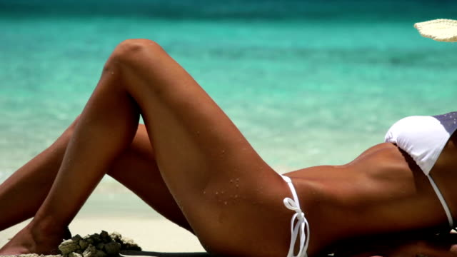 sexy woman sunbathing at a tropical Caribbean beach mid section of unrecognizable sexy woman sunbathing by the shore at a tropical Caribbean beach sunbathing stock videos & royalty-free footage