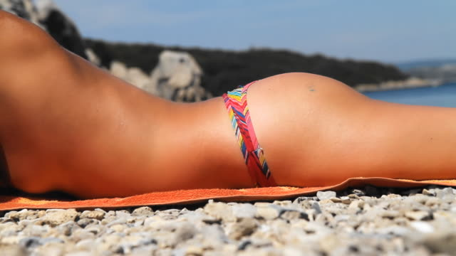 HD: Sexy Woman Sunbathing On The Beach HD1080p: Close-Up shot of an unrecognizable sexy woman in biking lying on front on the beach sunbathing stock videos & royalty-free footage
