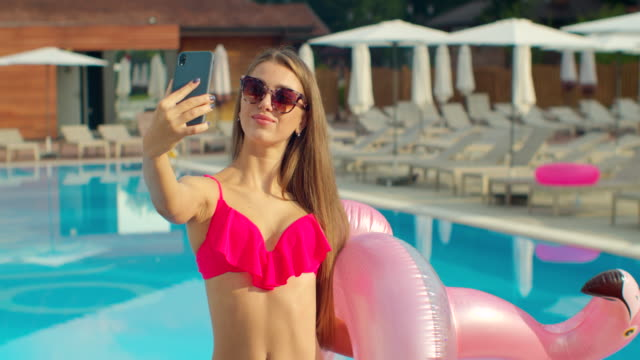 Sexy woman taking selfie photo on smartphone in swimming pool. Pool summer vacations.