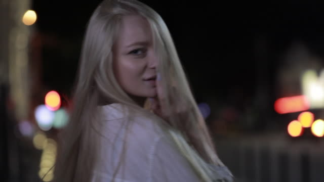 Sexy woman winking in night city video