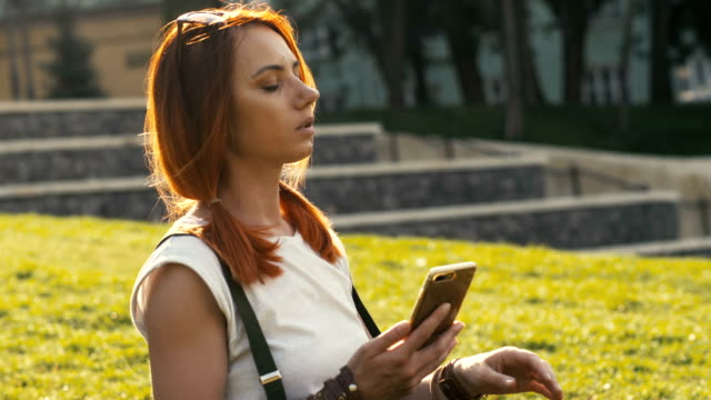 sexy woman with red hair holding and mobile phone on summer park - ragazza auricolari rossi video stock e b–roll