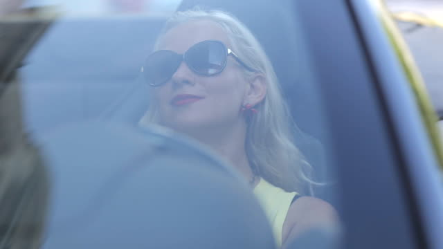 Sexy woman with red lipstick sitting behind the wheel of the cabriolet video
