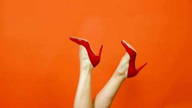 Sexy woman's legs in red high heels on a bright orange background. They swing from side to side. Red patent shoes. Slow motion