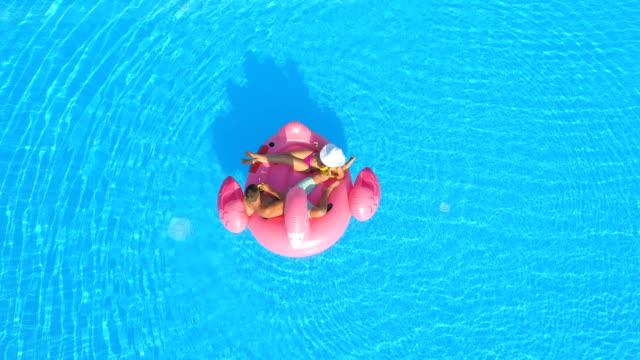 stockvideo's en b-roll-footage met luchtfoto: sexy jonge paar nippen cocktail dranken op roze flamingo float in zwembad - opblaasband