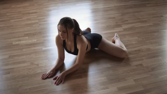 sexy young girl athlete stretched before training sitting on the floor sexy young girl athlete stretched before training sitting on the floor. doing the splits stock videos & royalty-free footage