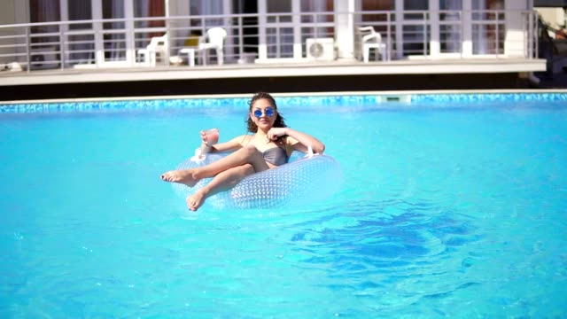 Sexy young girl with sunglasses, coctail and dreads on the inflatable rubber ring posing in the swimming pool. Slowmotion shot. video