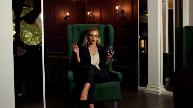 Sexy young lady sitting in a chair with a glass of red wine and a cigar.