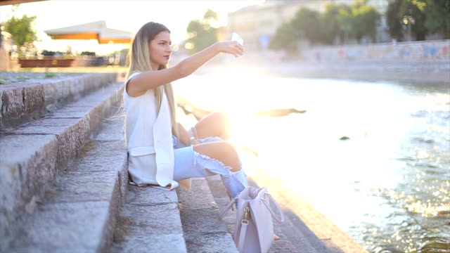 Sexy young stylish hipster woman posing and taking selfie video