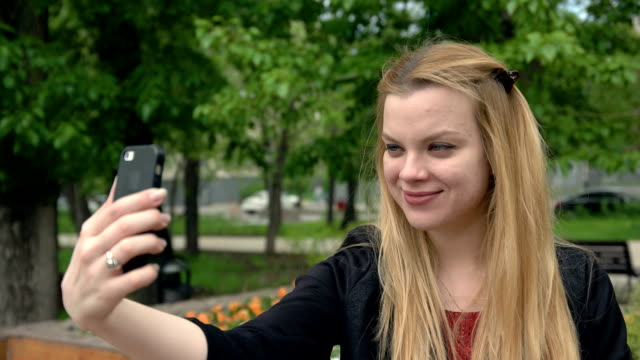Sexy young woman doing selfie on summer day in park. Smiling girl making selfie video