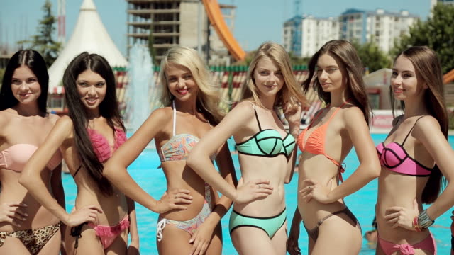 Sexy young women in bikinis posing by the pool in the summer Sexy young women in bikinis posing near the pool in the summer bikini stock videos & royalty-free footage
