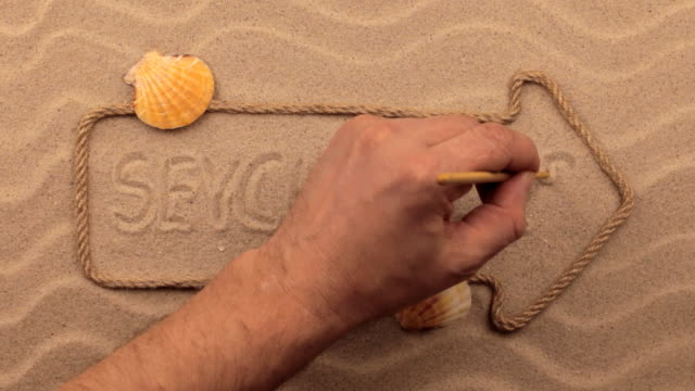 Seychelles inscription written by hand on the sand, in the pointer made from rope. video