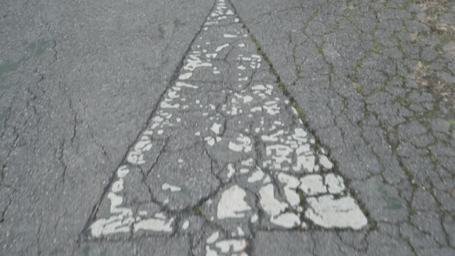 Shabby white arrow on cracked old gray asphalt. Road marking of the direction of movement