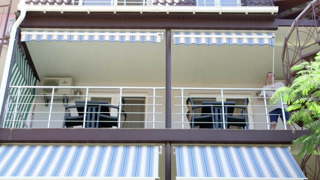 Shading balcony of summer hotel man unrolling retractable awning on a sunny day video