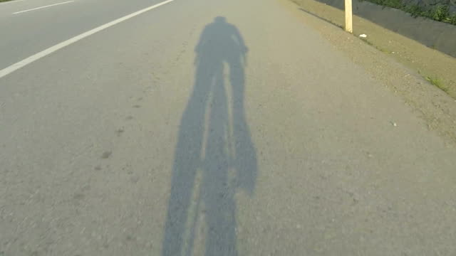 Shadow hitting the road on the sunset bicycle ride video