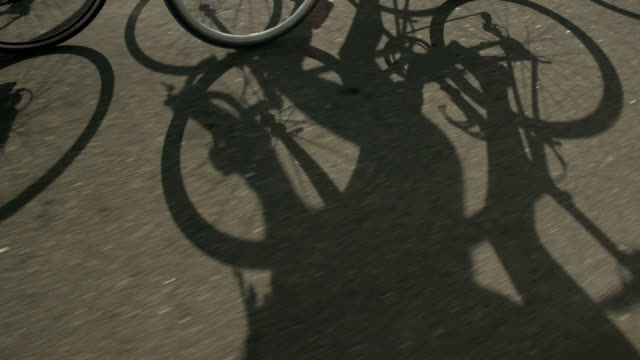 shadow of a cyclist athlete on a bicycle race. fast movement on the highway. - ciclismo su strada video stock e b–roll
