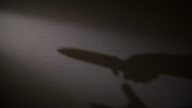 vidéos et rushes de une ombre d'une main tenant un couteau dans sa main. - lame