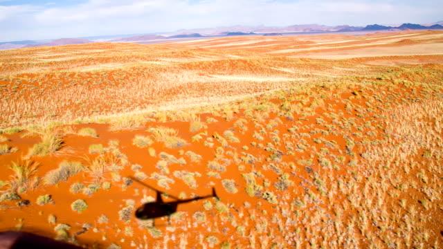 aerial schatten von einem hubschrauber in der namib - afrikanische steppe dürre stock-videos und b-roll-filmmaterial