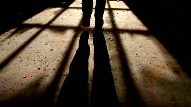 skuggan av en man gå iväg och håller pistolen i handen inuti vissa mörka, kusliga byggnad - kriminell bildbanksvideor och videomaterial från bakom kulisserna