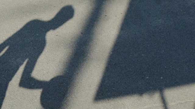 Shadow of basketball player dribbling the ball on playground, active lifestyle video