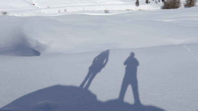 shadow of couple on snow, tilt up to village - livigno video stock e b–roll